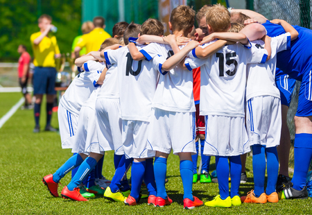 Photo for Coach giving young soccer team instructions. Youth soccer team together before final game. Football match for children. Boys group shout team, gathering. Coach briefing. Soccer football background. - Royalty Free Image