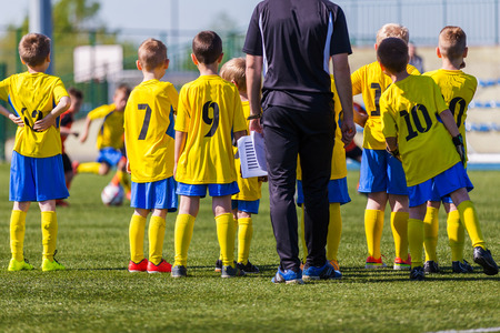 Photo pour Coach and youth soccer reserve players watching football match. Coach giving young soccer team instructions.  Coach briefing. Soccer football background. - image libre de droit