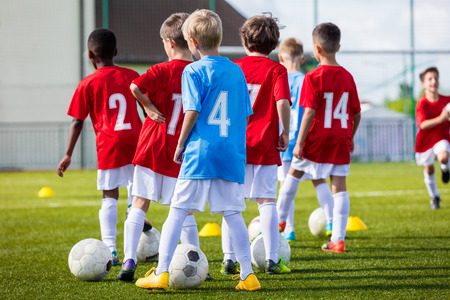 Foto de Football soccer training for youth boys team before the final tournament soccer match. Young boys kicking soccer ball on the stadium football pitch - Imagen libre de derechos