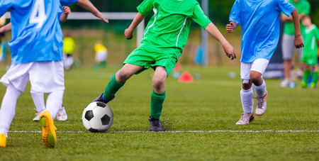 Photo for Youth soccer football teams kicking soccer ball on a sports pitch. Soccer tournament for young footballers. - Royalty Free Image