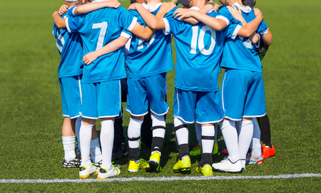 Kids with soccer coach gathering before match. Youth soccer football team. Group photo. Soccer players standing together united. Soccer team huddle. Teamwork, team spirit and teammate example.