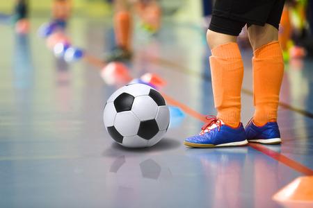 Foto de Children training soccer futsal indoor gym. Young boy with soccer ball training indoor football. Little player in light orange sports socks - Imagen libre de derechos