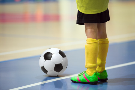 Foto de Football futsal training for children. Indoor soccer young player with a soccer ball in a sports hall. Player in yellow uniform. Sport background. - Imagen libre de derechos