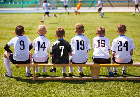 Foto de Football Players on Match Game. Young Soccer Team Sitting on Wooden Bench. Soccer Match For Children. Little Boys Playing Tournament Soccer Match. Youth Soccer Club Footballers - Imagen libre de derechos