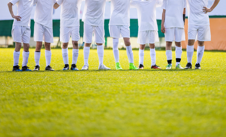 Youth Football Team. Young Soccer Players Standing in Row. Boys Standing Together During Penalty Shots. Boys in White Soccer Jersey Shirts