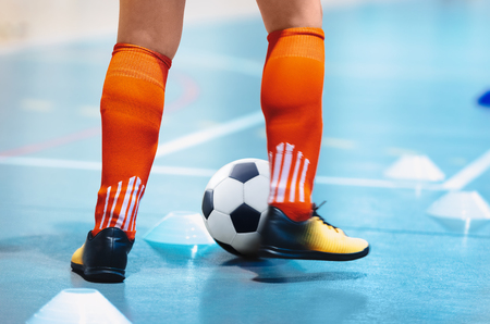 Futsal league. Indoor soccer player in futsal shoes training dribble drill with ball. Indoor soccer training. Running futsal player, soccer ball, white cones. Indoor football player with classic ball.