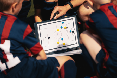 Photo pour Football Coach Board. Sports Football Education. Close-up of Coach Coaching Kids Using Magnetic Tactic Coach Clip Board. White Foootball Strategy White Board. Boys Listening Teacher/Coach - image libre de droit