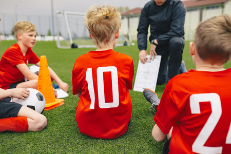 Photo pour Soccer Game Day Management. Coach Coaching Youth Soccer Team. Boys Listening Coach Inspirational and Tactics Speech. Coach Preparing Team for the Match - image libre de droit