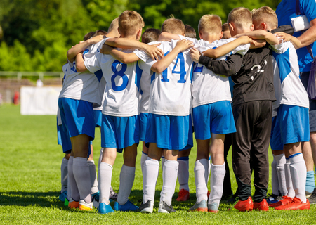Foto de Football Youth Team Huddling with Coach. Young Happy Boys Soccer Players Gathering Before the Final Match - Imagen libre de derechos