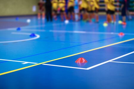 Photo pour Sports team on futsal training field. Indoor soccer training during the winter. Futsal training field with blue cones. Indoor football practice for children. Physical education unit of soccer - image libre de droit