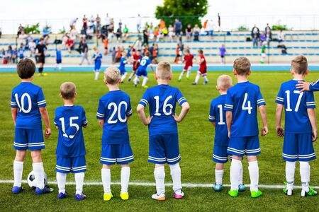Photo pour Junior Level Kids Sports Team. Football Soccer Children Players Standing Together with Coach During School Soccer Competition Game. Boys in Blue Soccer Jersey Sportswear and Soccer Cleats - image libre de droit
