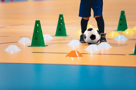 Indoor soccer players training with balls. Indoor soccer sports hall. Futsal league. Indoor football futsal player, ball, futsal floor and red cone. Futsal training dribbling drill. Sports background