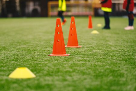 Photo for Sports Training Equipment on the Grass Pitch. Soccer Football Cones and Markers. Soccer Junior Players on Training Practice Unit in the Background - Royalty Free Image