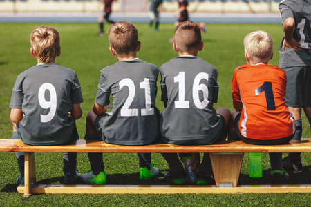 Boys in Football Team Sitting on Substitute Bench Ready to Play the Final Tournament Match. School Kids in Sports Uniforms With Player Numbers on Backs. Soccer Players in School Junior Level Team