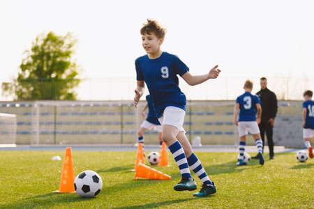Foto de Boys running after ball on soccer training unit. Children having fun on football practice session. School physical education class on summer day - Imagen libre de derechos