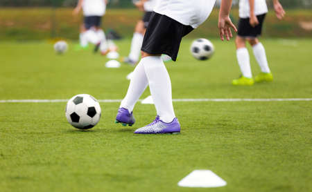 Photo pour Soccer Player Kicking Ball on Training. Group of Footballers Improving Skills on Practice Venue. Soccer Boy in Purple Cleats and White Soccer Jersey Kit - image libre de droit