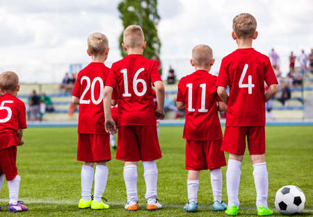 Photo pour Group of School Boys on Soccer Game Standing Along Sideline and Watching Competition. Football Tournament For Kids - image libre de droit