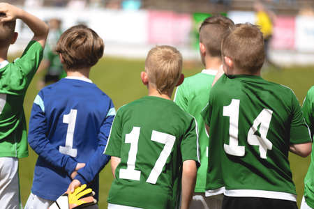 Photo pour Boys in Green Soccer Jersey Shirts Standing in a Team and Watching Football Tournament Match. Kids Playing Sports Outdoor in Summer Sunny Day - image libre de droit