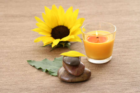 beautiful sunflower stack of pebbles and candle