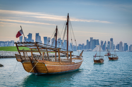 Dhows moored off Museum Park in central Doha, Qatar, with some of the buildings from the city\'s in the background.