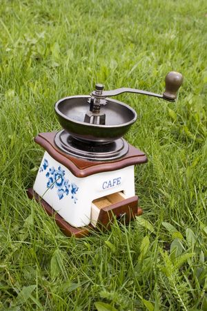 Old coffee grinder on grass 2