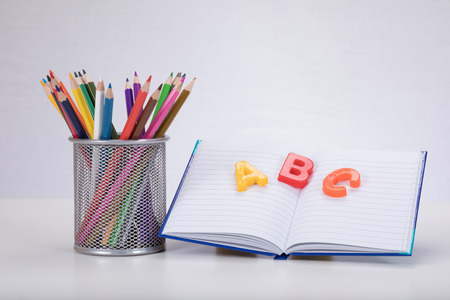 Foto de A school learning concept with colour drawing pencils an open book and ABC alphabet learning letters on a plain white background with copy space. - Imagen libre de derechos