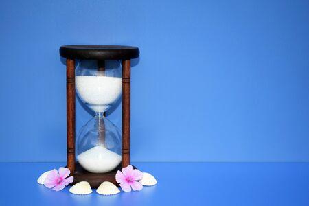 Photo pour Romantic concept with hourglass, flowers and seashells, copy space for text - image libre de droit