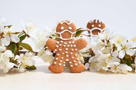 Photo for Gingerbread men with protective face mask surrounded by spring blooming twig - concept in coronavirus (COVID-19) time - Royalty Free Image