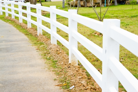 white fence at the roadside