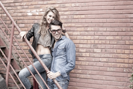 Photo pour Sexy and fashionable couple wearing jeans, shoot in a grungy location - landscape orientation with copy-space - image libre de droit