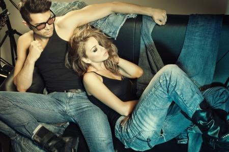 Foto de Sexy man and woman dressed in jeans doing a fashion photo shoot in a professional studio  - Imagen libre de derechos