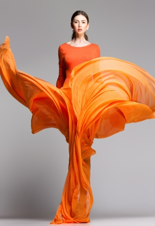 Foto de beautiful woman in long orange dress posing dynamic in the studio - Imagen libre de derechos