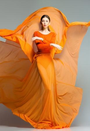 Photo for beautiful woman in long orange dress posing dynamic in the studio - Royalty Free Image