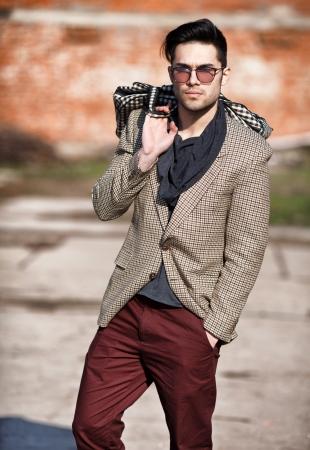 Foto de sexy fashion man model dressed elegant holding a bag posing outdoor - Imagen libre de derechos