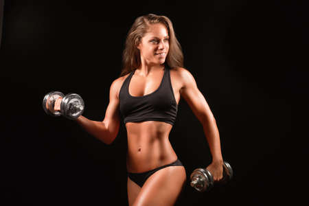 Photo for Closeup photo of a sports woman portrait wearing black sportswear over dark lifting dumbell - Royalty Free Image