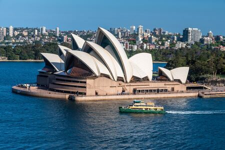 Photo for The Opera House in a sunny day with a blue sky on the background and surrounded by the sea water of the bay - Royalty Free Image
