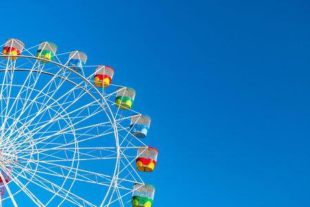 Photo pour Ferris wheel with colourful rainbow seats in Sydney on clear blue sky background - image libre de droit