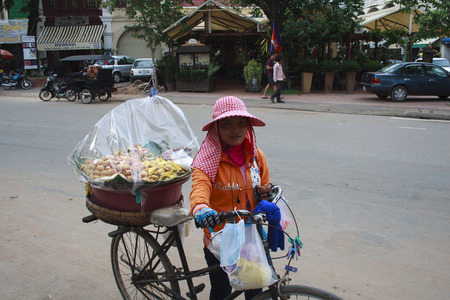 Siem Reap, Cambodia - April 30, 2013: A woman with bicycle who sold sweets on the street in Siem Reap Market in Cambodia