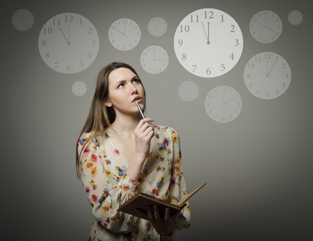Photo pour Thoughtful girl holding pen and notebook  Time concept  - image libre de droit