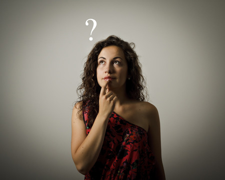 Girl full of doubts and hesitation. Girl and a question mark above head. Young woman doing something.