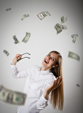 Rejoicing. Woman in white and falling dollar banknotes. Success, currency and lottery concept.