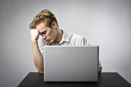 Photo pour Young man using a laptop to browse the net. Overtime and fatigue concept. - image libre de droit