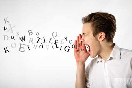 Young man is screaming at something. Screaming and letters concept.
