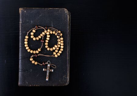 Photo for Rosary beads and prayer book. Rosary and book of Catholic Church liturgy on dark background. - Royalty Free Image