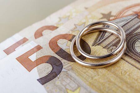 Foto de Two wedding rings and currency. Wedding or divorce concept. Wedding Planning concept. Expenses. - Imagen libre de derechos