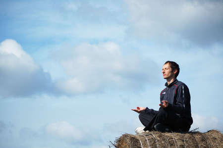 Meditative young man on the sky background
