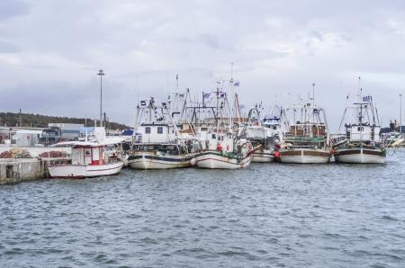 Photo pour fishing boats in a harbor, under cloudy sky - image libre de droit