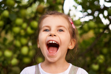 Portrait of a cute little girl making an excited face with her mouth wide openの写真素材