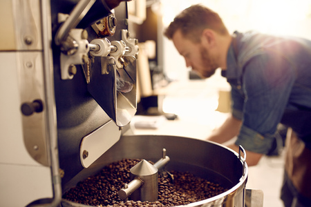 Photo pour Dark and aromatic coffee beans in a modern roasting machine with the blurred image of the professional coffee roaster visible in the background - image libre de droit
