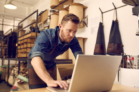 Photo for Handsome young male business owner looking serious while working on his laptop with a neat and tidy workshop behind him - Royalty Free Image